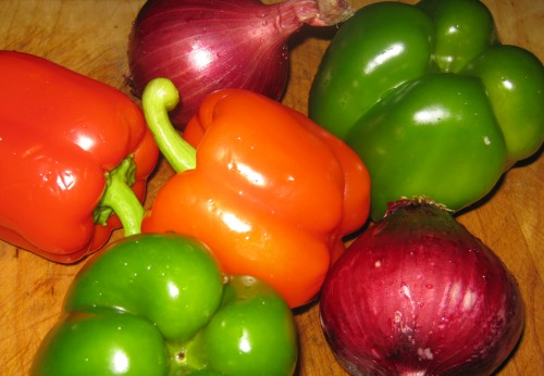 Whole bell peppers and red onions on a cutting board