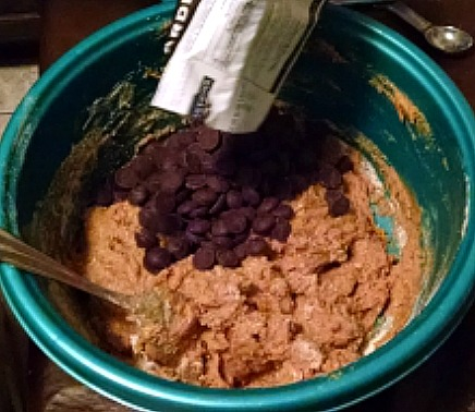 Cookie dough with chocolate chips being poured in