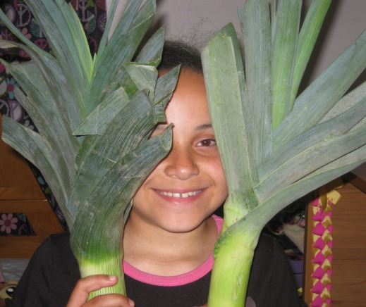 Child holding two giant leeks