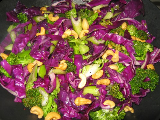 Wok filled with purple cabbage broccoli and cashews