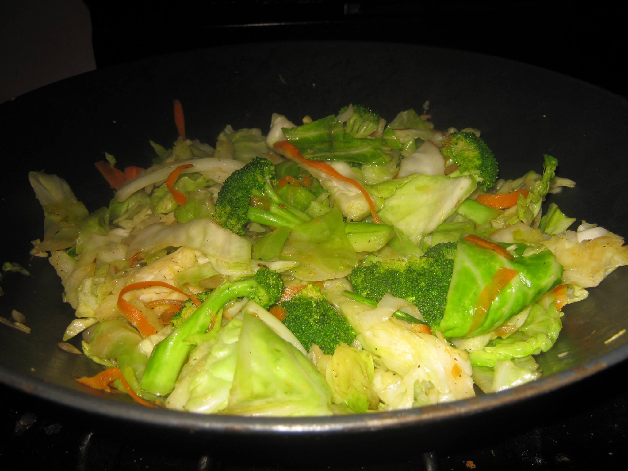 Cooked green cabbage, carrots, broccoli and onions recipe in a wok