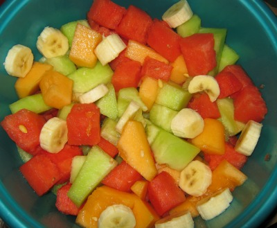Fruit bowl containing watermelon, bananas, and orange and green cantaloupe